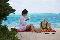 A woman sitting on beach with wine glass in hand