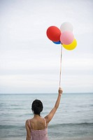 A woman holding balloons in beach