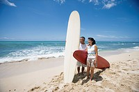 A couple standing with surfboards at beach