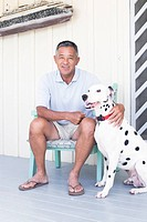 Mature man sitting on chair with dog