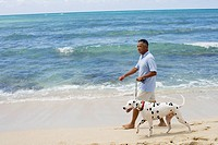 Man walking with dog at beach