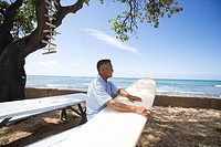 Mature man sitting on bench with surfboard (thumbnail)