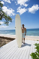 Mature man standing with surfboard (thumbnail)