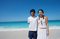 A young couple standing on beach