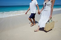 Low section of a couple holding hands and walking at beach