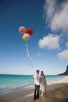 A young couple holding balloons at beach