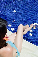 Elevated view of a woman sitting beside swimming pool