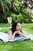 A smiling young woman relaxing in garden (thumbnail)