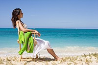 A young woman sitting on chair at beach (thumbnail)
