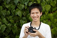 Portrait of a young man holding camera (thumbnail)