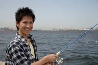 Portrait of a young man holding a fishing rod