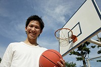 Portrait of a young man holding basketball