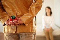 Husband holding gift behind back, rear view