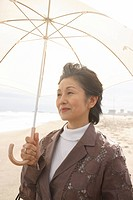Senior woman with umbrella at beach (thumbnail)