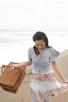 Teenage girl 14_15 with picnic basket at beach