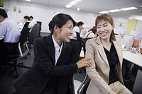A woman sharing a joke with her colleague in the office