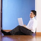 Side profile of a businessman sitting on the floor holding a laptop