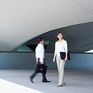 Businesswoman and a businessman walking on a pedestrian walkway