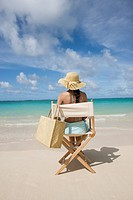 Rear view of a woman sitting on chair at beach
