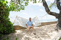 Mature man sitting on hammock