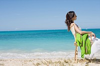 Side view of a young woman sitting on chair at beach