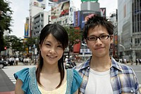 Portrait of a young couple smiling with buildings in background