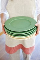 Teenage girl 14_15 holding stack of plates, close_up