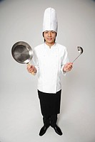 Chef holding frying pan and ladle, portrait