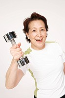 Senior woman holding dumbbell, smiling, portrait