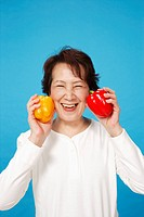 Senior woman holding red and yellow bell pepper, close_up