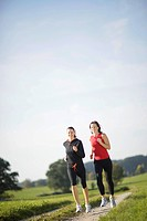 Two women running along dirt road, Munsing, Bavaria, Germany