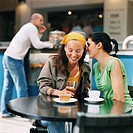 female friends sitting in cafe gossiping