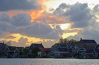 Historical houses at the river Zaan under cloudy sky at sunset, Zaandijk, Netherlands, Europe