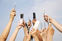 Group of people raising mobile phones against sky, close_up