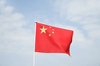 Chinese flag waving in wind, low angle view