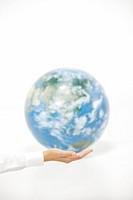 Businessman holding hand against globe, close_up