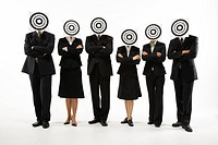 Group of businesspeople standing in line with bull´s eye on face