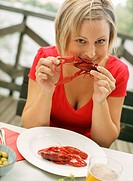 Portrait of woman eating crayfish