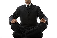 Businessman meditating, low section, close_up