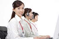 Three businesswomen using computer and headset, smiling
