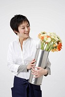 Young woman holding flower vase, smiling