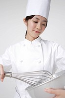 Female chef using whisk and mixing bowl, smiling, close_up