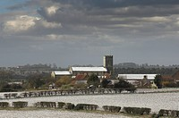 View of snow covered farmland, village and church, Wighton, Norfolk, England, march