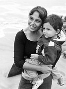 A smiling woman holding a boy in her arms on a sandy beach BW.