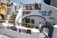 Woman at Atlantis Books bookshop in the sunlight, Oia, Santorini, Greece, Europe