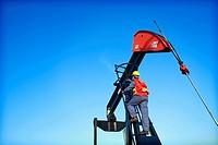 Worker climbing pumpjack, Alberta, Canada