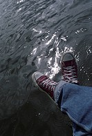 Low section view of a person's feet hanging over water