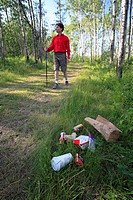 Middle age male hiking on forest trail with garbage on the ground.