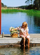 Girl with basket of summer wildflowers on wooden dock with feet in water