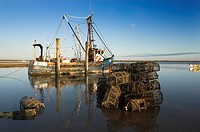 Fishing Boat at high tide, with lobster and crab pots, Brancaster Staithe, Norfolk, England, january